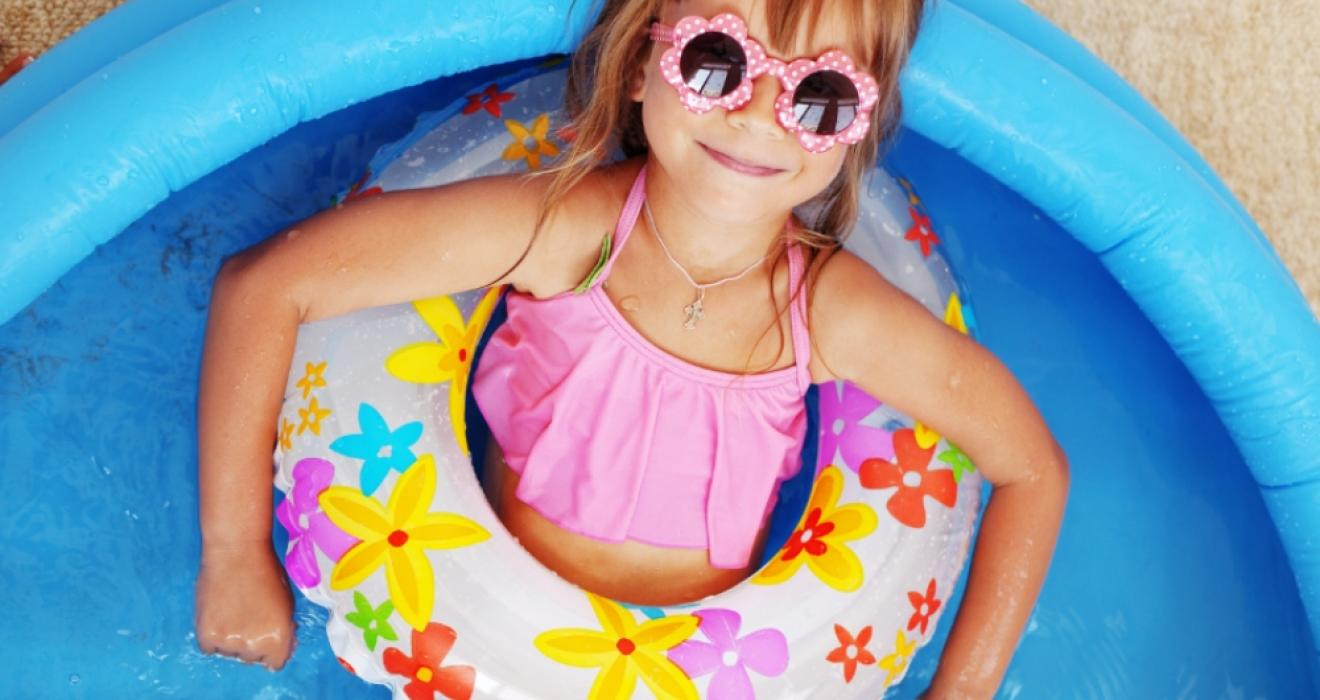 Child laying in a rubber ring in a paddling pool