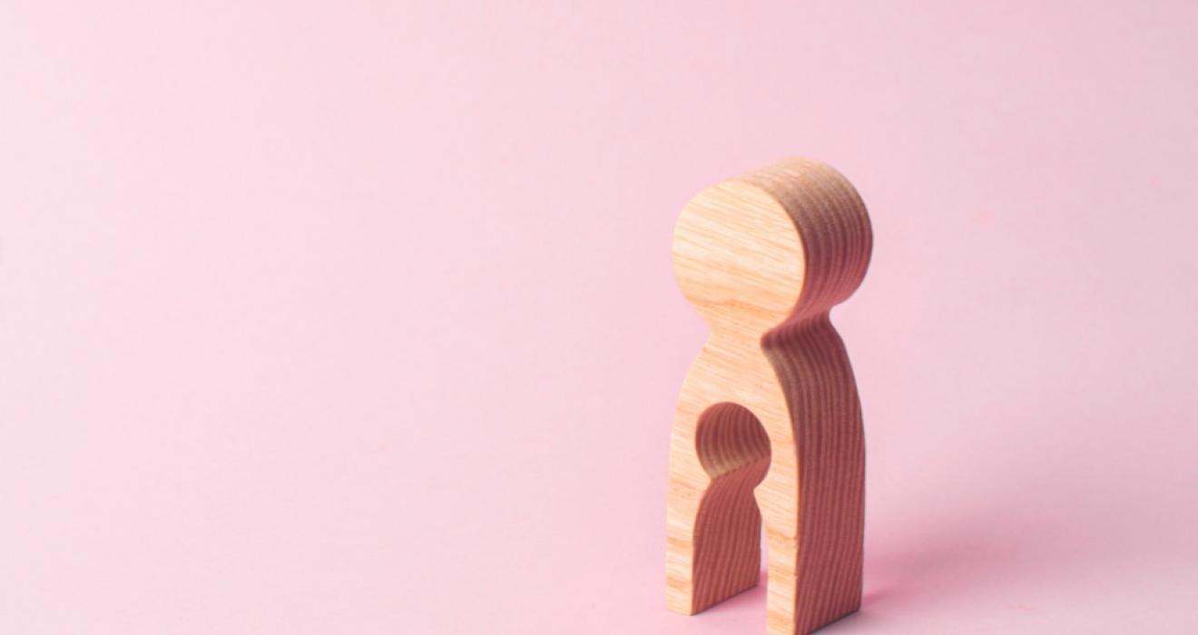 Picture of a wooden figure with a baby shaped gap in