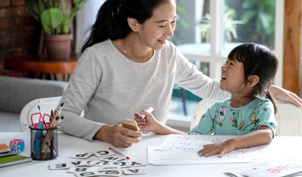 Picture of a happy mum and child sat at a table learning about letters