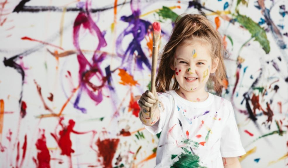 Picture of a child making a mess painting on a wall
