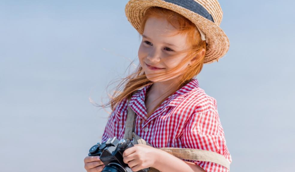 Picture of red headed child smiling holding a camera