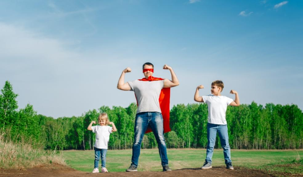 A picture of a super dad wearing a cape with his two children