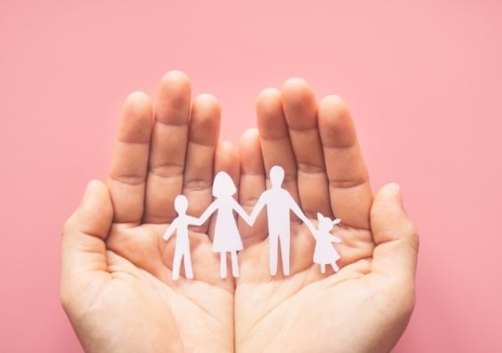 Hand holding family paper cut on pink background. Family day concept