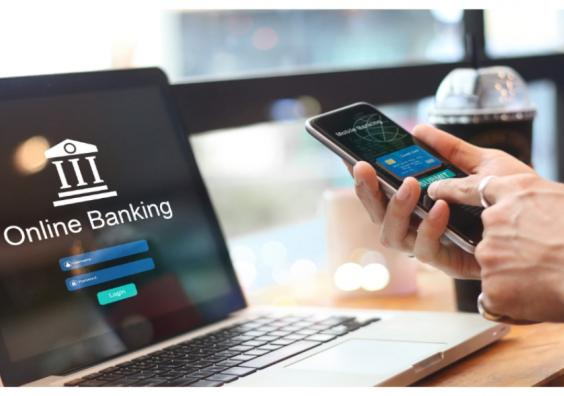 picture of someone logging into online banking on a laptop with a smart phone