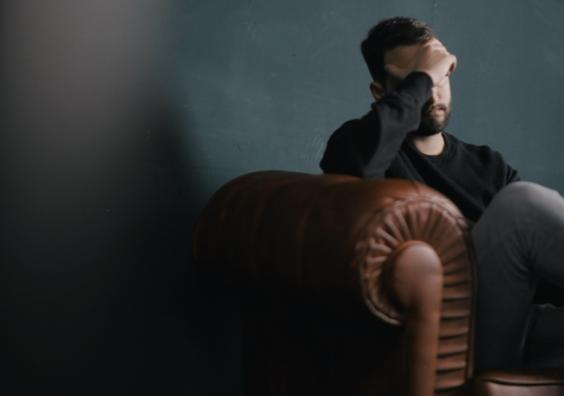 Photo of a man sat on a sofa with his head in his hands