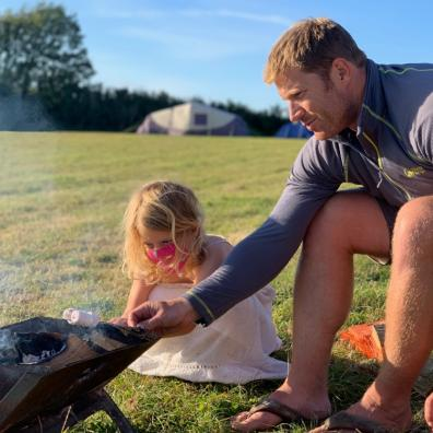 Picture of a father and daughter toasting marshmallows whilst camping