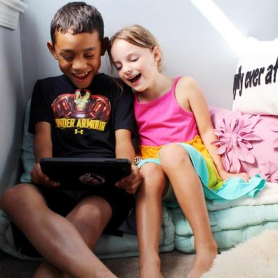 Picture from Natterhub of a boy and girl playing on an electronic device