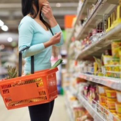 Picture of a woman with a basket in a supermarket shopping isle