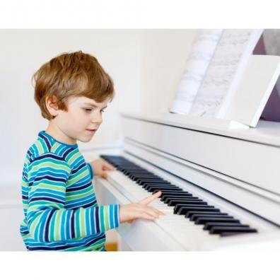 Picture of a healthy young boy playing the piano