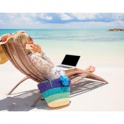 Picture of a business woman working on a beach with her phone and laptop