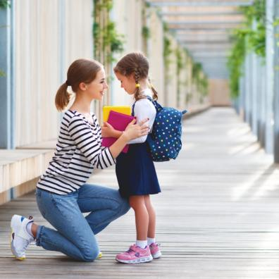 Picture of a child with her mum on her first day of school