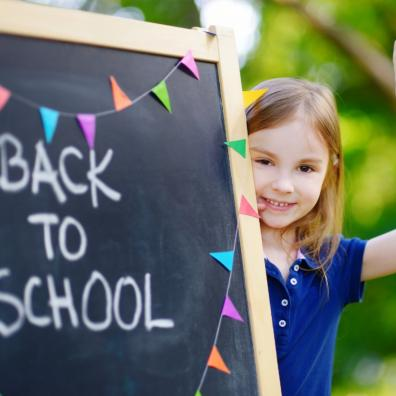 Picture of girl stood next to a chalkboard with back to school written on it