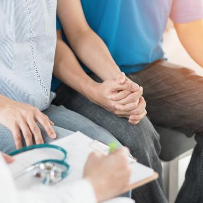 Picture of a couple holding hands in a fertility doctors office