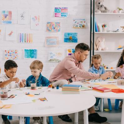 Picture of teacher and interracial children drawing pictures together at tables in school classroom
