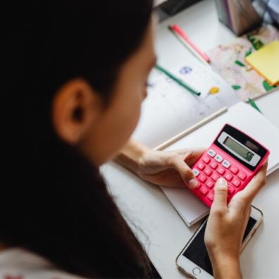 Picture of a girl learning about finance with a calculator