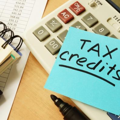 Picture of Tax credits written on a post it note with a calculator and notebook