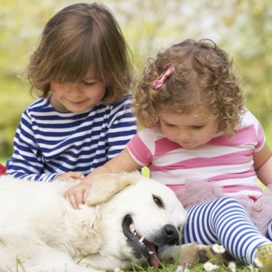 Picture of two young children stroking their pet dog