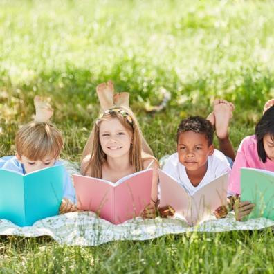 primary school children reading books in a field of grass