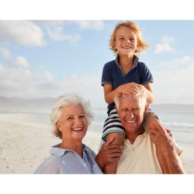 Picture of grandparents with their grandchild on their shoulders at the beach