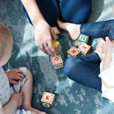 Children sitting down with blocks with letters on