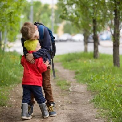Picture of siblings hugging eachother out on a grassy pathway